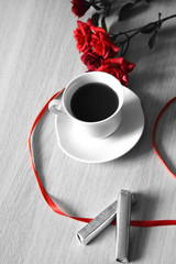 cup of coffee with red ribbon and roses