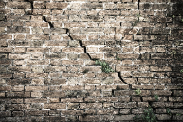 Cracked brick wall - Deep crack in a brick wall - toned image