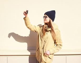 Fashion pretty blonde makes selfie-portrait on the smartphone, c