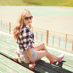Pretty blonde in sunglasses relaxing in the city, street fashion