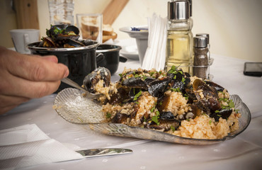 Lunch time. Plate with mussels with rice.