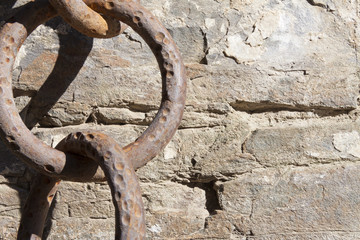 Old, big rusty iron chain on rock