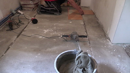 Bucket of cement adhesive glue and man measure tiles on floor