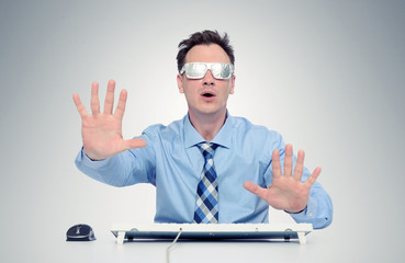 Businessman with glasses of foil in front of computer