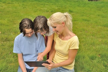 Family sitting on the lawn and using digital tablet