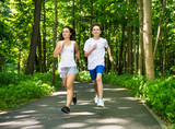 Teenage girl and boy running in park