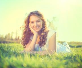 Beauty romantic girl lying on summer field outdoors
