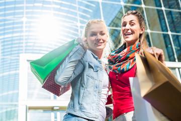 Freudinnen shoppen mit Einkaufstüten in Stadt