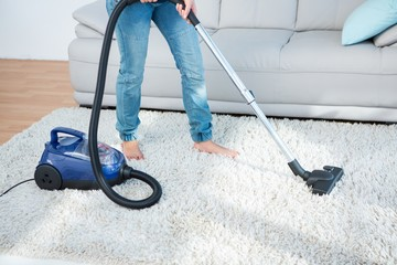 Woman using vacuum cleaner on carpet