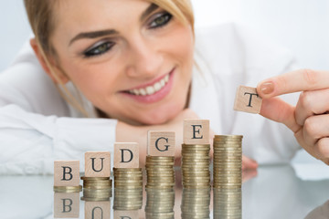 Businesswoman With Budget Blocks On Stacked Coins