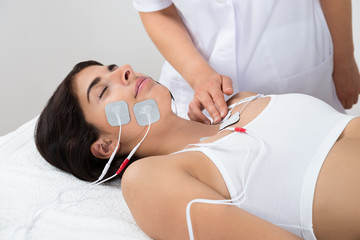 Woman Lying With Electrodes On Chest And Face