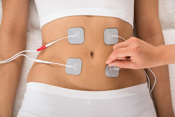 Therapist Placing Electrodes On Woman's Stomach