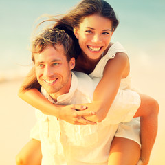 Romantic couple having fun piggyback on beach