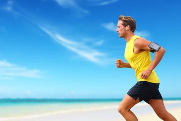 Runner running listening smartphone music on beach