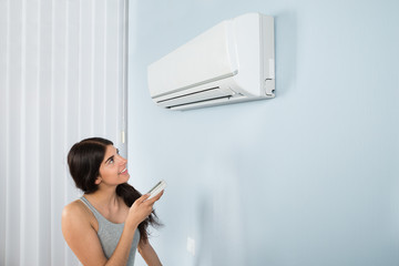 Woman Holding Remote Control Air Conditioner