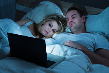 Couple Looking At Laptop In Bedroom