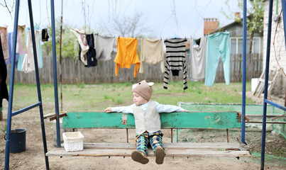The kid shakes on a swing in the village