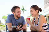 Couple on cafe looking at smart phone app pictures
