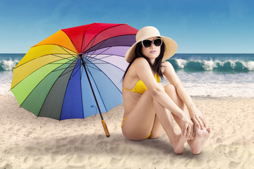 Cute woman with umbrella at shore