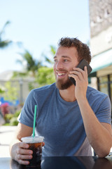 Man on cafe using smartphone talking on cell phone