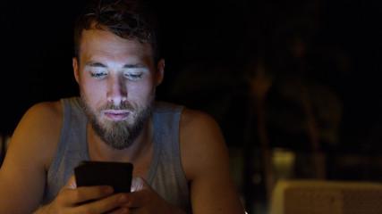 Man using smartphone at night browsing internet