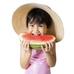 Girl with hat eats watermelon in studio
