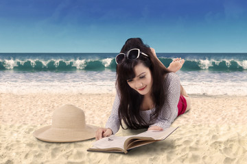 Pretty woman reading book on the beach