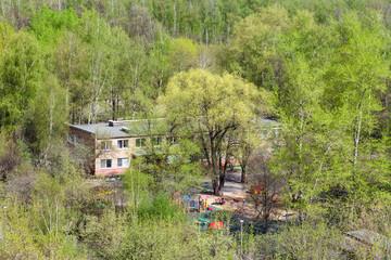 kindergarten in green woods in sunny day