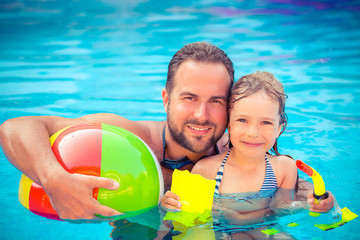 Child and father playing in swimming pool