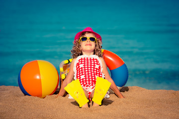 Happy child sitting on the beach