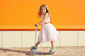 Little girl in dress on the scooter against the colorful wall ba
