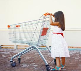 Little girl with shopping cart outdoors near shop