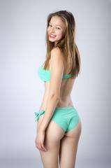 Mujer joven en bikini de espaldas sonriendo