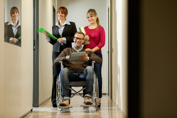 Businessman on a wheelchair with his colleagues