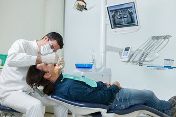 dentist is doing a checkup on a 40 years old man