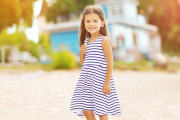 Summer travel portrait of beautiful little girl on the beach