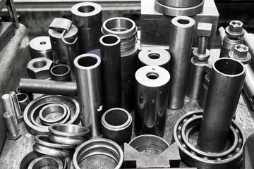 Steel cylinders, pistons and tools in workshop. Industry theme.