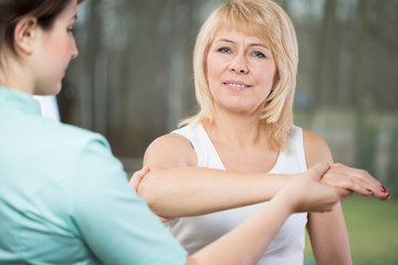 Physical therapist diagnosing painful arm