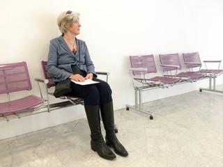 Ältere Frau sitzt abwartend auf Sessel