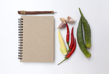 Vegetable and blank notebook on white background