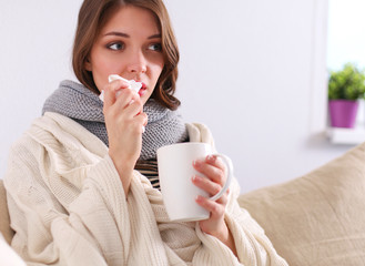 Sick woman covered with blanket holding cup of tea sitting on