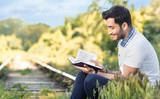 Man reading book. Sideways or profile. Outdoor, outside