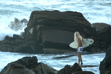 Beautiful blond surfer girl about to enter the sea