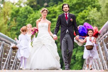 Hochzeitpaar mit Blumenkindern auf Brücke