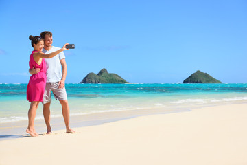 Couple on beach vacation taking selfie smartphone