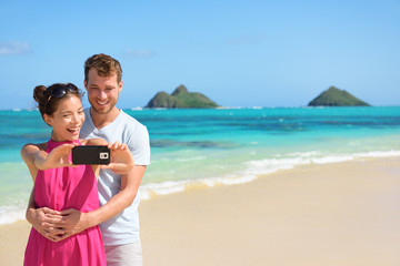 Beach vacation couple taking selfie on smartphone