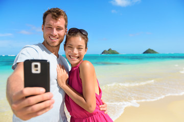 Smartphone - beach vacation couple taking selfie