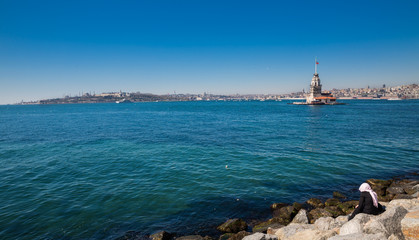 Maiden's Tower lighthouse with sea and muslim woman in Istanbul