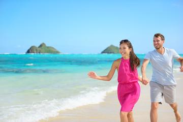 Beach couple happy running having fun on Hawaii
