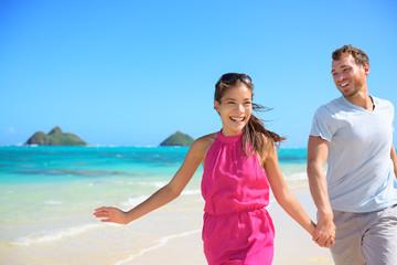 Happy couple on beach running having fun on Hawaii